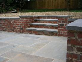 Bluestone Patio With Brick Sitting Wall And Stairs